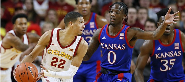 Iowa State guard Tyrese Haliburton (22) looks to pass the ball around Kansas guard Marcus Garrett (0) during the first half of an NCAA college basketball game Wednesday, Jan. 8, 2020, in Ames, Iowa. (AP Photo/Charlie Neibergall)