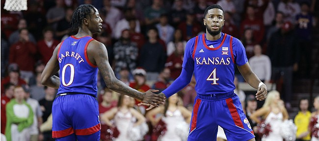 Kansas' Marcus Garrett (0) and Isaiah Moss (4) slap hands during the first half of the team's NCAA college basketball game against Oklahoma in Norman, Okla., Tuesday, Jan. 14, 2020.