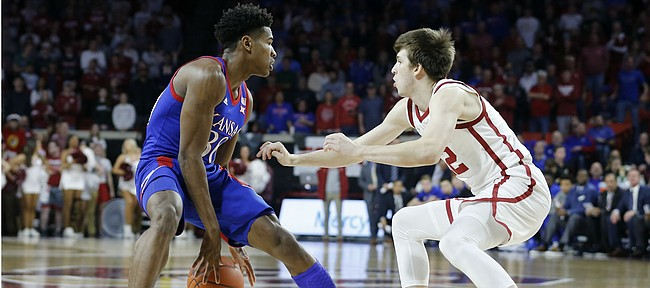 Kansas' Ochai Agbaji (30) is defended by Oklahoma's Austin Reaves during the first half of an NCAA college basketball game in Norman, Okla., Tuesday, Jan. 14, 2020.