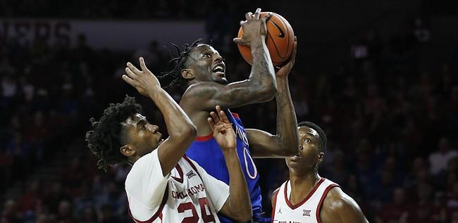 Kansas' Marcus Garrett (0) shoots between Oklahoma's Jamal Bieniemy (24) and Kristian Doolittle (21) during the first half of an NCAA college basketball game in Norman, Okla., Tuesday, Jan. 14, 2020.