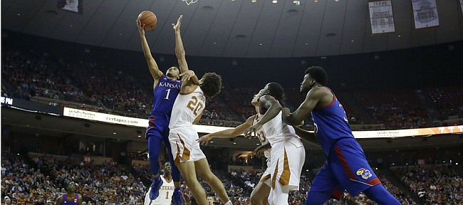Kansas guard Devon Dotson (1) shoots over Texas forward Jericho Sims (20) during the first half of an NCAA college basketball game, Saturday, Jan. 18, 2020, in Austin, Texas. (AP Photo/Eric Gay)
