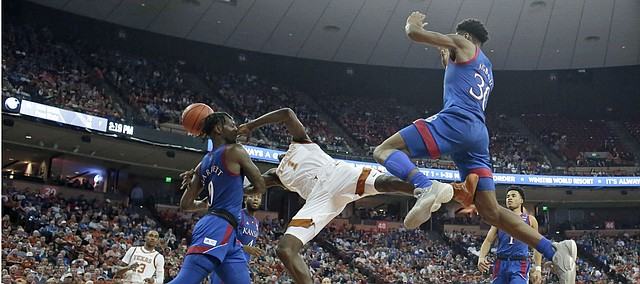 Texas guard Andrew Jones (1) is fouled by Kansas guard Marcus Garrett (0) as he tries to score during the second half of an NCAA college basketball game, Saturday, Jan. 18, 2020, in Austin, Texas. (AP Photo/Eric Gay)