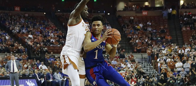 Kansas guard Devon Dotson (1) drives around Texas guard Courtney Ramey (3) during the first half of an NCAA college basketball game, Saturday, Jan. 18, 2020, in Austin, Texas. (AP Photo/Eric Gay)