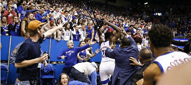 Kansas forward Silvio De Sousa (22) picks up a chair during a brawl following the Jayhawks' win against Kansas State, Tuesday, Jan. 21, 2020 at Allen Fieldhouse.