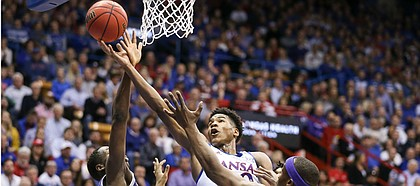 Kansas guard Ochai Agbaji (30) lunges to the bucket between Kansas State forward Montavious Murphy (23) and Kansas State forward Makol Mawien (14) during the first half, Tuesday, Jan. 21, 2020 at Allen Fieldhouse.