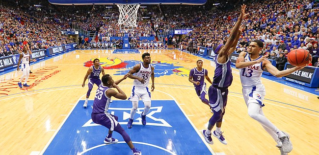 Kansas guard Tristan Enaruna (13) sweeps around to throw a pass during the second half, Tuesday, Jan. 21, 2020 at Allen Fieldhouse.