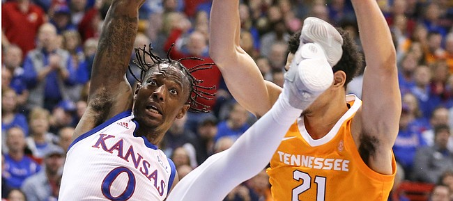 Kansas guard Marcus Garrett (0) is sent to the floor after a hard foul from Tennessee forward Olivier Nkamhoua (21) during the first half, Saturday, Jan. 25, 2019 at Allen Fieldhouse.