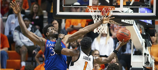 Oklahoma State guard Jonathan Laurent (1) leans on Kansas center Udoka Azubuike (35) while taking a shot during the second half of an NCAA college basketball game in Stillwater, Okla., Monday, Jan. 27, 2020. Kansas defeated Oklahoma State 65-50. (AP Photo/Brody Schmidt)