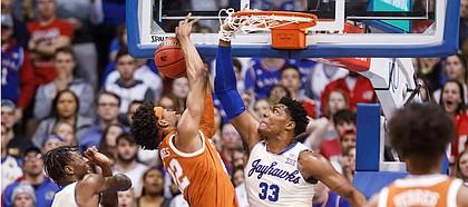 Kansas forward David McCormack (33) get his hand caught in the net after stuffing a shot by Texas forward Kai Jones during the first half on Monday, Feb. 3, 2020 at Allen Fieldhouse.