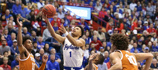 Kansas guard Devon Dotson (1) gets to the bucket against several Texas defenders during the first half on Monday, Feb. 3, 2020 at Allen Fieldhouse.