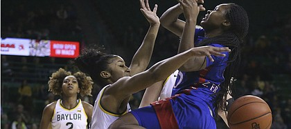 Kansas guard Zakiyah Franklin (15) loses the ball as she collides with Baylor guard Te'a Cooper (4) while driving to the basket in the first half of an NCAA college basketball game Wednesday, Feb. 5, 2020, in Waco, Texas. (AP Photo/ Jerry Larson)