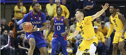 Kansas guard Isaiah Moss (4) is defended by West Virginia guard Jordan McCabe (5) as Kansas guard Marcus Garrett watches during the second half of an NCAA college basketball game Wednesday, Feb. 12, 2020, in Morgantown, W.Va. (AP Photo/Kathleen Batten)