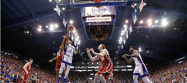 Kansas guard Devon Dotson (1) gets in for a bucket past Oklahoma guard Jamal Bieniemy (24) during the first half on Saturday, Feb. 15, 2020 at Allen Fieldhouse.