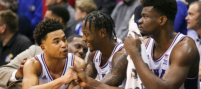 Kansas guards Devon Dotson, left, and Marcus Garrett have a laugh on the bench next to Kansas center Udoka Azubuike (35) with little time remaining in the game on Saturday, Feb. 15, 2020 at Allen Fieldhouse.