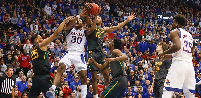Kansas guard Ochai Agbaji (30) gets tangled with Baylor guard Jared Butler (12) and Baylor forward Tristan Clark (25) while competing for a rebound during the first half on Saturday, Jan. 11, 2020 at Allen Fieldhouse.