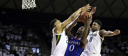 Baylor forward Tristan Clark, left, and Baylor guard Mark Vital, right, defend Kansas guard Marcus Garrett, center, under the basket during the first half of an NCAA college basketball game on Saturday, Feb. 22, 2020, in Waco, Texas. (AP Photo/Ray Carlin)