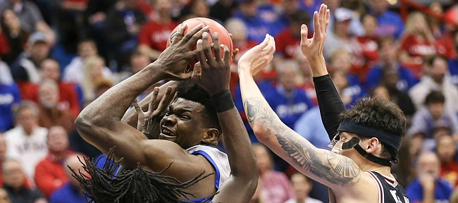 Kansas center Udoka Azubuike is doubled teamed by Oklahoma State guard Isaac Likekele (13) and Oklahoma State guard Lindy Waters III (21) during the first half on Monday, Feb. 24, 2020 at Allen Fieldhouse.
