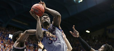 Kansas center Udoka Azubuike (35) powers through a triple team to the bucket during the second half against Oklahoma State on Monday, Feb. 24, 2020 at Allen Fieldhouse.