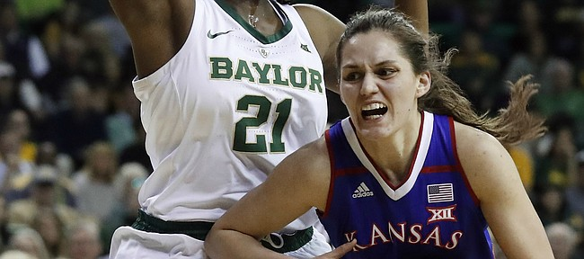 Baylor center Kalani Brown (21) defends as Kansas forward Mariane de Carvalho (4) drives to the basket during the first half of an NCAA college basketball game in Waco, Texas, Wednesday, Feb. 20, 2019. (AP Photo/Tony Gutierrez)