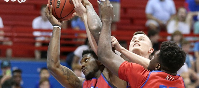 Kansas forward Silvio De Sousa battles for a rebound with Kansas forward Mitch Lightfoot and Kansas center Udoka Azubuike (35) during a scrimmage on Tuesday, June 11, 2019 at Allen Fieldhouse. In back is Kansas guard Ochai Agbaji (30).