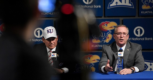Kansas Athletics Director Jeff Long, right, answers a question at a press conference introducing new football coach Les Miles, left, on Sunday, Nov. 18, 2018, at Hadl Auditorium.