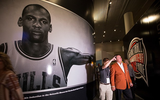 Kansas head coach Bill Self makes his way past a large portrait of Michael Jordan as he takes a tour through the Naismith Memorial Basketball Hall of Fame in Springfield, Massachusetts following a jacket presentation ceremony on Thursday, Sept. 7, 2017. On Friday, Self will be inducted into the Hall of Fame