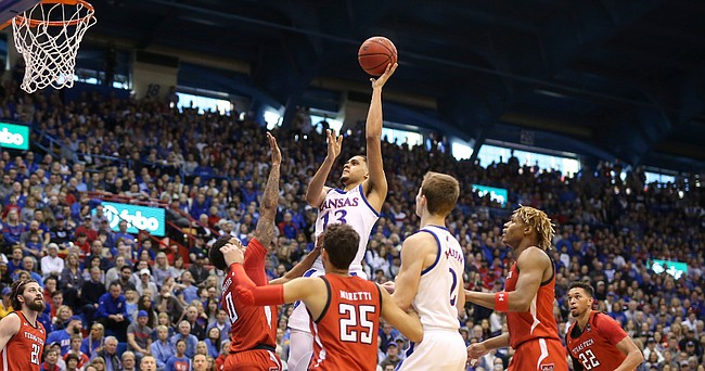 Kansas guard Tristan Enaruna (13) turns for a bucket over the Texas Tech defense during the first half, Saturday, Feb. 1, 2020 at Allen Fieldhouse.