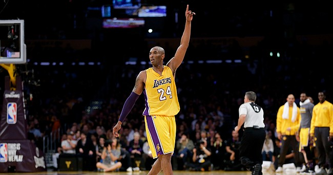 Los Angeles Lakers forward Kobe Bryant gestures during the first half of Bryant's last NBA basketball game, against the Utah Jazz, on Wednesday, April 13, 2016, in Los Angeles. Former Kansas forward Tarik Black, standing in a gray T-Shirt on the Lakers bench, is in the background.