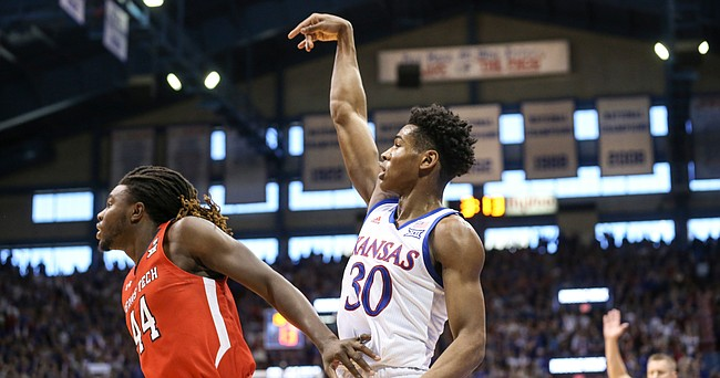 Kansas guard Ochai Agbaji (30) hangs his hand after hitting a three over Texas Tech guard Chris Clarke (44) from the corner during the first half, Saturday, Feb. 1, 2020 at Allen Fieldhouse.