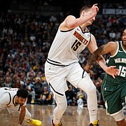 Milwaukee Bucks guard Frank Mason III (15) drives past Denver Nuggets center Nikola Jokic (15) in the second half of an NBA basketball game Monday, March 9, 2020, in Denver.