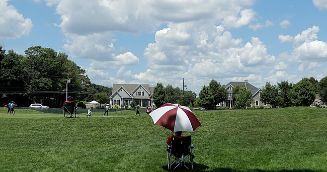 A volunteer uses an umbrella while watching golfers pass on the seventh fairway during the second round of the Travelers Championship golf tournament at TPC River Highlands, Friday, June 26, 2020, in Cromwell, Conn.