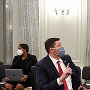 University of Mississippi Vice Chancellor for Intercollegiate Athletics Keith Carter, left, talks with Southeastern Conference Commissioner Greg Sankey, right, before they testify at a Senate Commerce Committee hearing on Capitol Hill in Washington, Wednesday, July 1, 2020. The hearing is looking at the National Collegiate Athletic Association Board of Governors' recent report on student-athlete compensation and the modernization of rules related to name, image, and likeness (NIL) commercialization.