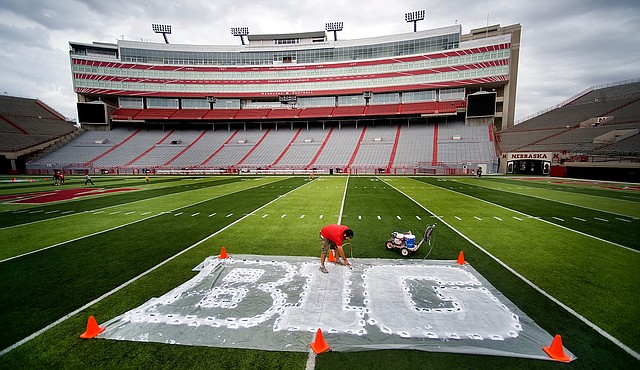 In this Thursday, Oct. 6, 2011 file photo, Turf manager Jared Hertzel touches up the newly-painted Big Ten conference logo on the football field at Memorial Stadium in Lincoln, Neb.