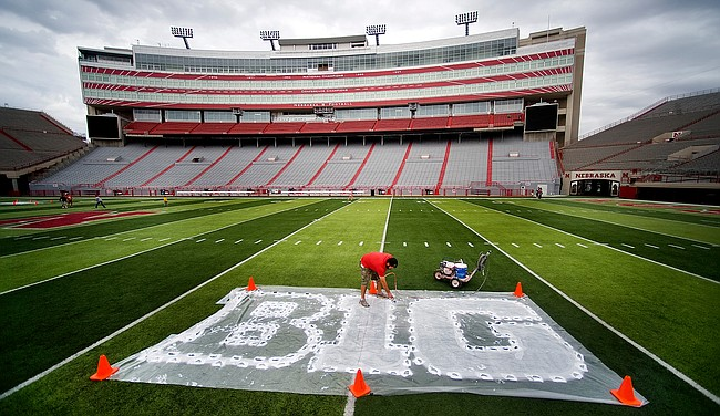 In this Thursday, Oct. 6, 2011 file photo, Turf manager Jared Hertzel touches up the newly-painted Big Ten conference logo on the football field at Memorial Stadium in Lincoln, Neb. The Big Ten Conference announced Thursday, July 9, 2020 it will not play nonconference games in football or several other sports this fall because of the coronavirus pandemic.