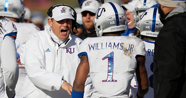 Kansas head coach Les Miles, left, congratulates Kansas running back Pooka Williams, right, after a touchdown by Williams during the second half of an NCAA college football game against Iowa State, Saturday, Nov. 23, 2019, in Ames, Iowa. Iowa State won 41-31. (AP Photo/Matthew Putney)