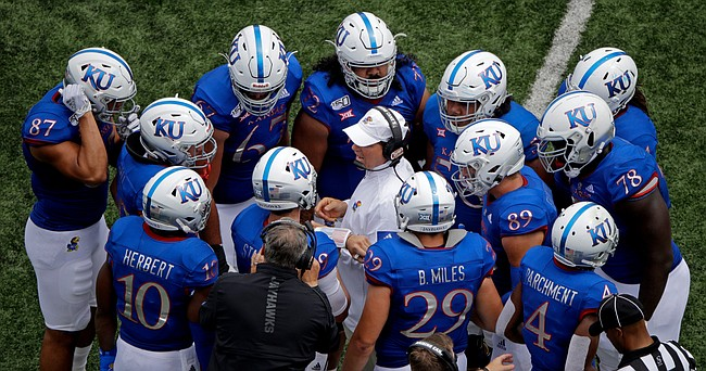 Kansas head coach Les Miles talks to his players during a time out in the second half of an NCAA college football game against Indiana State, Saturday, Aug. 31, 2019, in Lawrence, Kan. Kansas won 24-17. AP Photo/Charlie Riedel)