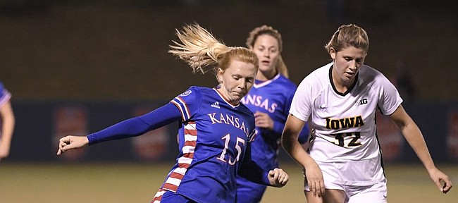 Ceri Holland fires in a cross against Iowa Saturday night at Rock Chalk Park on Nov. 16, 2019.