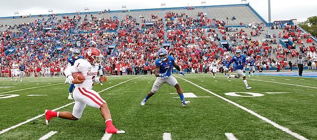 Oklahoma quarterback Jalen Hurts (1) runs up the sideline as Kansas safety Davon Ferguson (7) closes in during the second quarter on Saturday, Oct. 5, 2019 at Memorial Stadium.