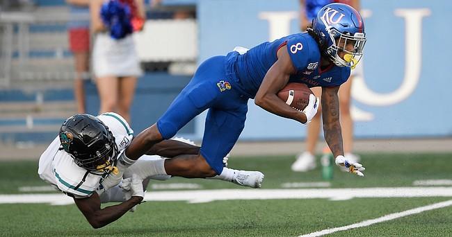 Kansas wide receiver Kwamie Lassiter Jr. is taken down on a return by Coastal Carolina's Jordan Morris Saturday night at David Booth Kansas Memorial Stadium on Sept. 7, 2019.