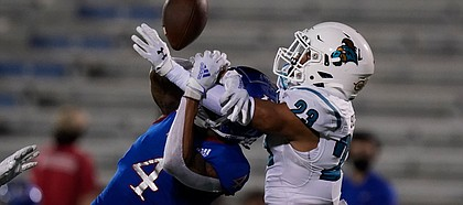 Coastal Carolina cornerback Derick Bush (23) is called for pass interference against Kansas wide receiver Andrew Parchment (4) during the second half of an NCAA college football game in Lawrence, Kan., Saturday, Sept. 12, 2020. Coastal Carolina defeated Kansas 38-23. (AP Photo/Orlin Wagner)
