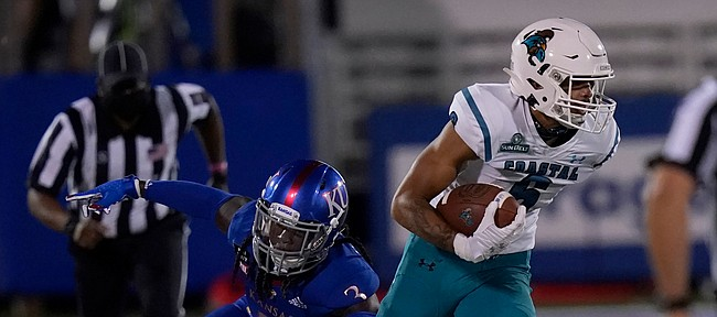 Kansas safety Ricky Thomas (3) tries to tackle Coastal Carolina wide receiver Jaivon Heiligh (6) during the first half of an NCAA college football game in Lawrence, Kan., Saturday, Sept. 12, 2020. (AP Photo/Orlin Wagner)