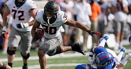 Oklahoma State running back Chuba Hubbard (30) breaks away from Kansas cornerback Johnquai Lewis (11) during the first half of an NCAA college football game in Lawrence, Kan., Saturday, Oct. 3, 2020.