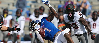 KU junior Pooka Williams Jr. is taken down by the Oklahoma State defense during KU's 47-7 loss to the Cowboys on Saturday, Oct. 3, 2020 at David Booth Kansas Memorial Stadium.