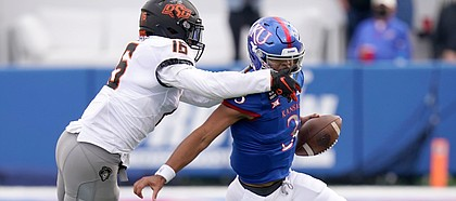 Kansas quarterback Miles Kendrick tries to avoid pressure from Oklahoma State's Devin Harper during a Jayhawks loss on Oct. 3, 2020.