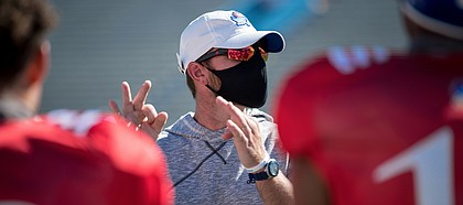 Kansas football offensive coordinator and quarterbacks coach Brent Dearmon addresses players during a preseason practice in August of 2020.