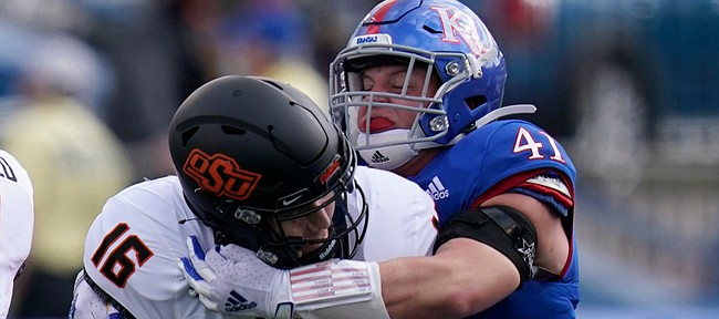 Oklahoma State quarterback Shane Illingworth (16) is sacked by Kansas safety Nick Channel (41) during the first half of an NCAA college football game in Lawrence, Kan., Saturday, Oct. 3, 2020. (AP Photo/Orlin Wagner)