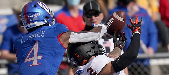 Kansas cornerback Elijah Jones (4) breaks up a pass intended for Oklahoma State wide receiver Tylan Wallace (2) during the first half of an NCAA college football game in Lawrence, Kan., Saturday, Oct. 3, 2020.