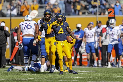 Oct 17, 2020; Morgantown, West Virginia, USA; West Virginia Mountaineers safety Alonzo Addae (4) celebrates after making an interception during the first quarter against the Kansas Jayhawks at Mountaineer Field at Milan Puskar Stadium.