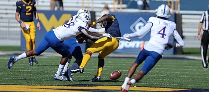 MORGANTOWN, WV - OCTOBER 17: West Virginia Mountaineers wide receiver T.J. Simmons (1) fumbles lbles after bring hit by Kansas Jayhawks linebacker Denzel Feaster (18) after catching a pass during the first quarter of the college football game between the Kansas Jayhawks and the West Virginia Mountaineers on October 17, 2020, at Mountaineer Field at Milan Puskar Stadium in Morgantown, WV.
