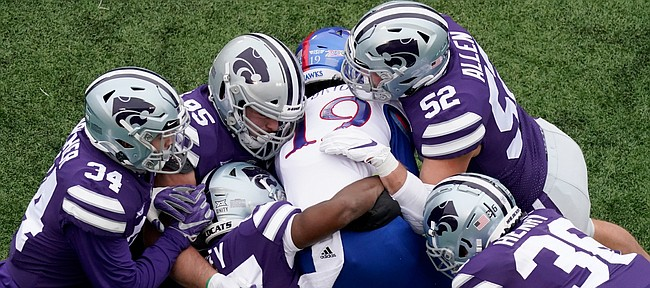 Kansas wide receiver Steven McBride (19) is tackled by a group of Kansas State defenders during the second half of an NCAA football game Saturday, Oct. 24, 2020, in Manhattan, Kan. (AP Photo/Charlie Riedel)